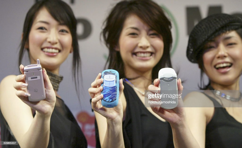 Models demonstrate mobile phone handsets from Japan's mobile communication giant NTT DoCoMo equipped with Sony's IC card technology FeliCa at a press...