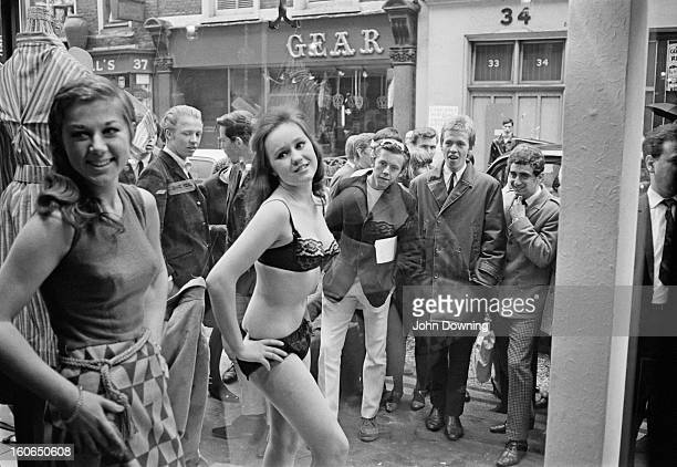Models Diane James and Jina Baker take part in a risque photoshoot in the window of a new Henry Moss boutique in Carnaby Street London 11th May 1966