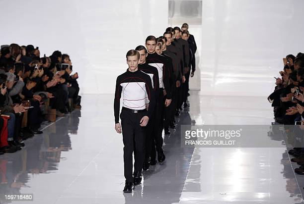Models display creations by Belgian designer Kris Van Assche for the label Dior during the men's FallWinter 20132014 collection show on January 19...