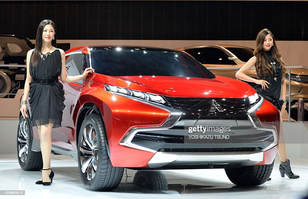 Models display Japanese automaker Mitsubishi Motors' concept plugin hybrid vehicle 'Concept XRPHEV' at the press preview of the Tokyo Motor Show in...