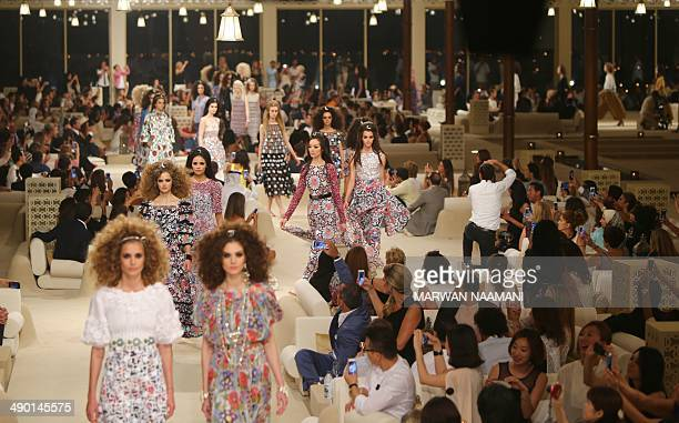Models display outfits from the Chanel 2015 Cruise runway collection at The Island in Dubai a man made island in the shape of a palm tree on May 13...
