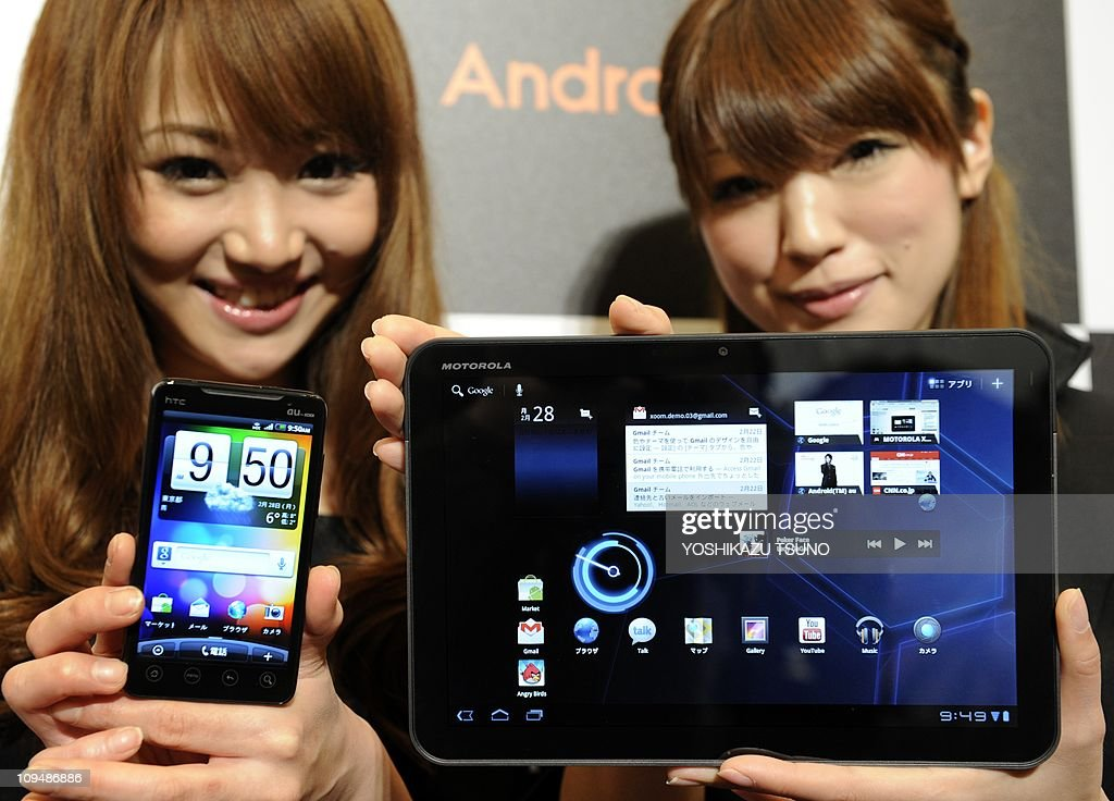 Models display Taiwanese electronics giant HTC's smartphone 'HTC EVO Wimax' (L) and US electronics giant Motorola's tablet computer 'Xoom' as Japanese telecommunicaion giant KDDI introduces Japanese market at a Tokyo hotel on February 28, 2011. The Android OS based smartphone and tablet will go on sale here in April. AFP PHOTO / Yoshikazu TSUNO