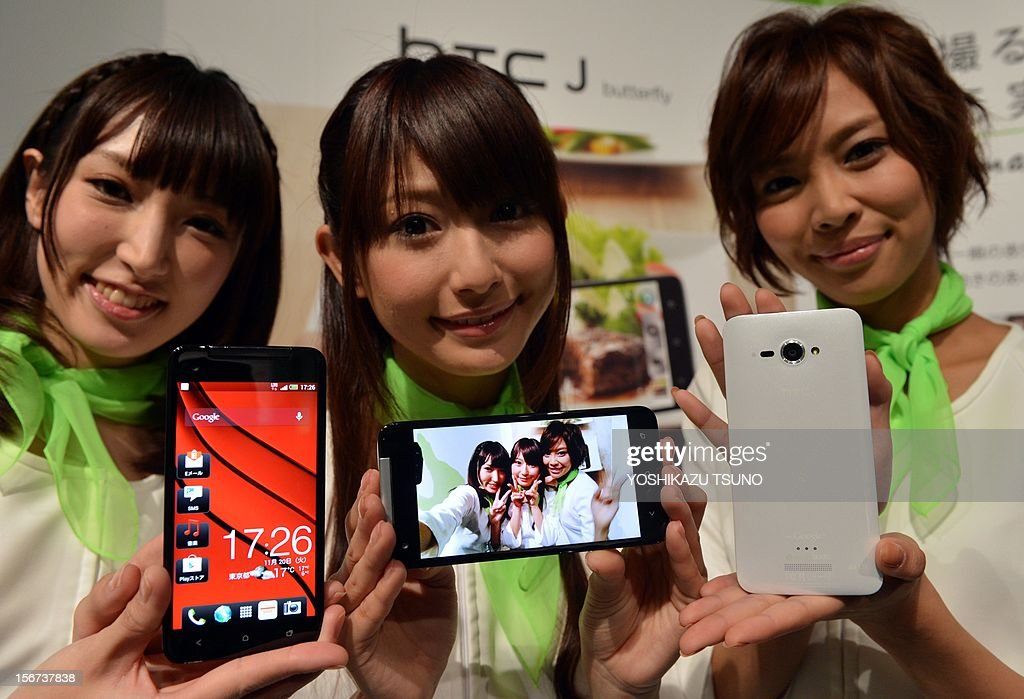 Models display Taiwan's electronics giant HTC's new smartphone 'HTCJ butterfly' for Japanese mobile carrier KDDI in Tokyo on November 20, 2012. The new smartphone has a quad-core CPU, 5-inch sized high-definition LCD display and an 8 mega-pixel CMOS camera on its slim body. AFP PHOTO / Yoshikazu TSUNO