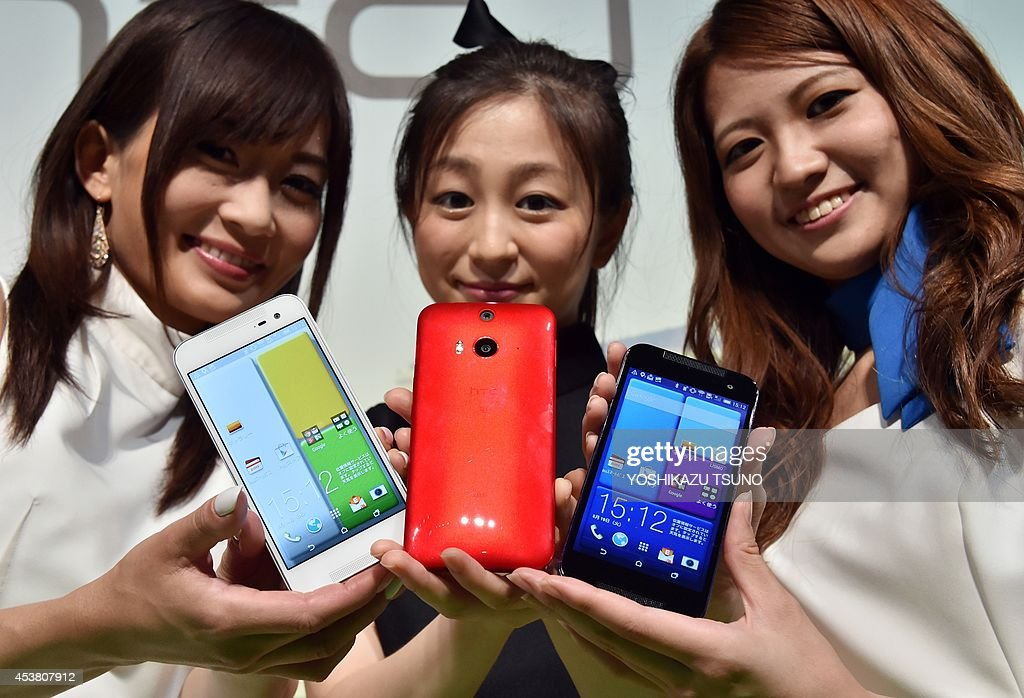 Models display the new smart phone of Taiwanese electronics maker HTC 'HTC J butterfly HTL23' at the launch event in Tokyo on August 19, 2014. The new HTC butterfly will go on sale through KDDI shops in Japan from August 29. AFP PHOTO / Yoshikazu TSUNO