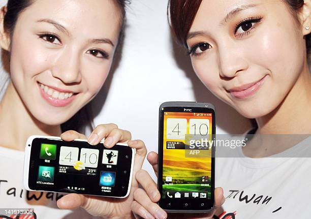 Models display the 'One' series new models of Taiwan's smartphone maker HTC during a press conference in Taipei on March 26 2012 The new series...
