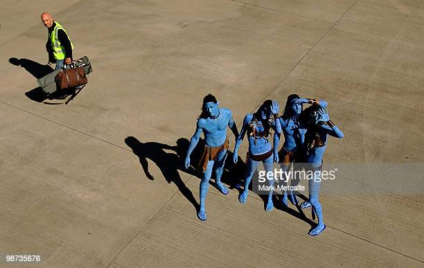 Models dressed up as characters from the film 'Avatar' pose on the tarmac as a baggage handler walks past during the launch of 'AVATAR' Bluray and...