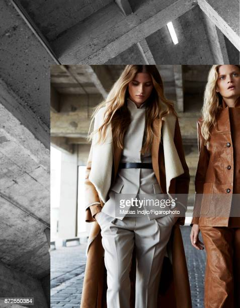 Models pose at a fashion shoot for Madame Figaro on September 19 2017 in Paris France Left Coat trench suit and belt Right Jacket and pants MANDATORY...