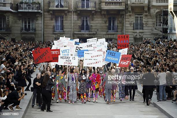 Models fake a demonstation as they present creations for Chanel next to German fashion designer Karl Lagerfeld during the 2015 Spring/Summer...