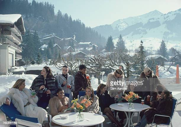 Models from Parisian jeweller M Gerard enjoying drinks on the terrace of The Palace Hotel in Gstaad Switzerland 1984