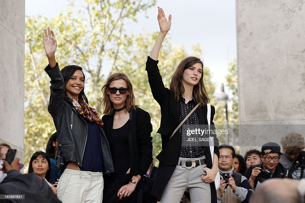 Models gesture as they stand in front of the Palais de Tokyo prior to the start of the Gosia Baczynska 2014 Spring/Summer ready-to-wear collection fashion show, on October 2, 2013 in Paris.