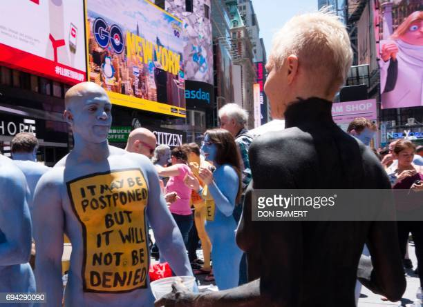Models get their bodies painted in Times Square while being watched by the public June 9 2017 in New York The models displayed personal messages as a...