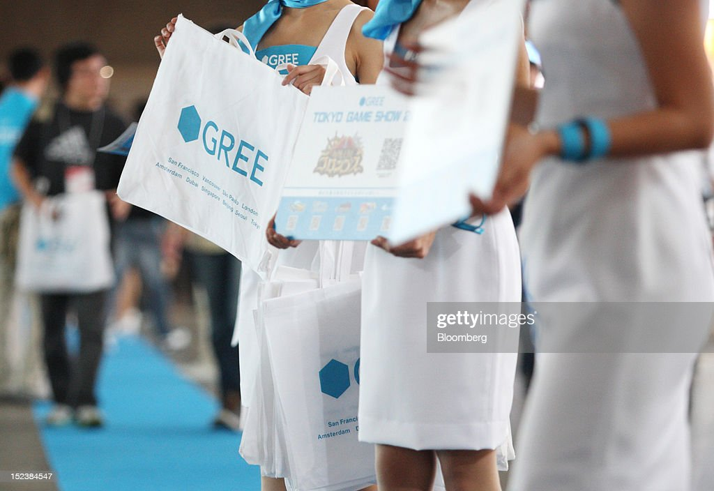 Models hold bags bearing the logo of Gree Inc. at the Tokyo Game Show 2012 at Makuhari Messe in Chiba, Japan, on Thursday, Sept. 20, 2012. The show will be held through Sept. 23. Photographer: Tomohiro Ohsumi/Bloomberg via Getty Images