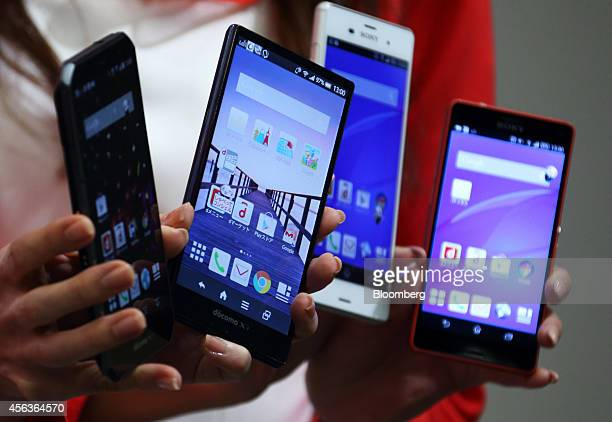 Models hold Fujitsu Ltd Arrows from left Sharp Corp Aquos Zeta Sony Corp Xperia Z3 and Xperia Z3 Compact smartphones during a news conference...