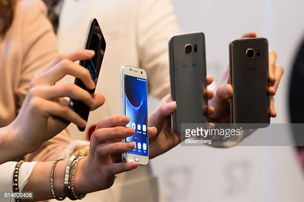 Models hold Samsung Electronics Co's Galaxy S7 and Galaxy S7 Edge smartphones for photographs during a media event in Seoul South Korea on Thursday...