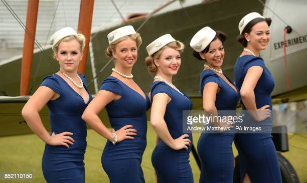 Models in period style Air Hostess dresses pose infront of a vintage biplane at the Goodwood Revival