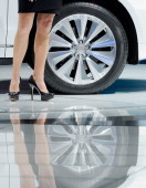 A models legs standing next to the wheel of an Audi car is reflected on the Los Angeles Convention floor during the Los Angeles Auto show on November...