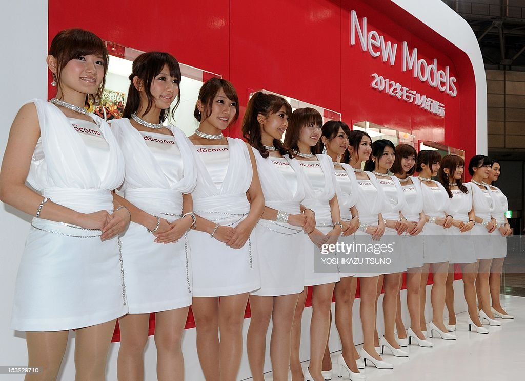 Models line up to greet visitors at the booth of Japanese mobile communications company NTT DoCoMo at Asia's largest electronics trade show CEATEC (Cutting-Edge IT & Electronics Comprehensive Exhibition) in Chiba, suburban Tokyo on October 2, 2012. Some 600 Japanese and foreign companies exhibited their latest technology and products. AFP PHOTO / Yoshikazu TSUNO