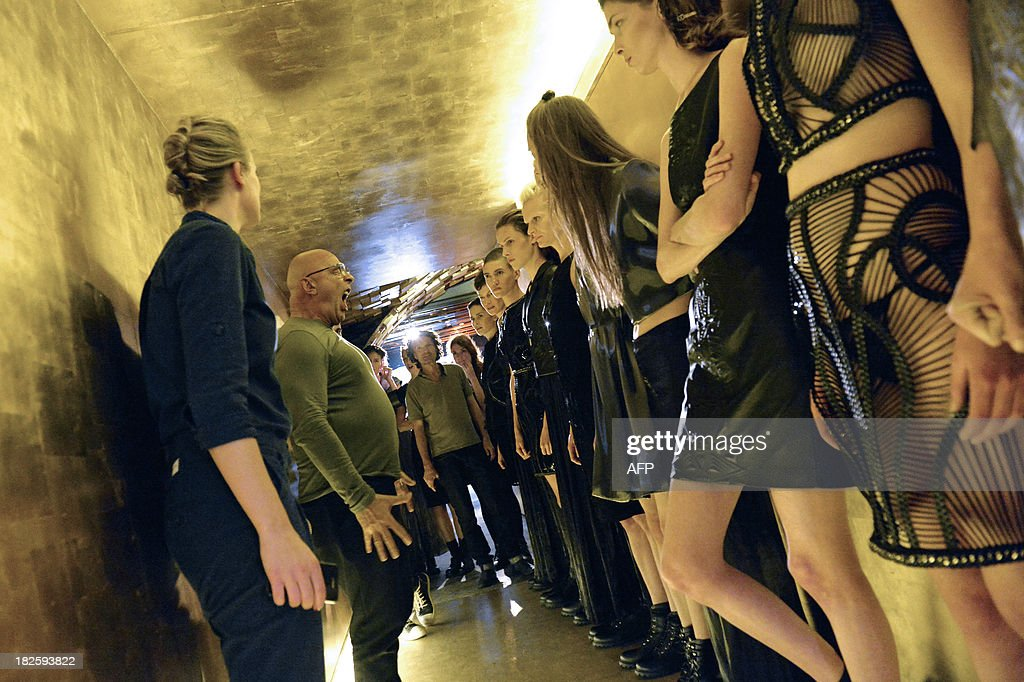 Models listen instructions of French photographer Jean-Baptiste Mondino (2ndL) before the start of the Iris Van Herpen 2014 Spring/Summer ready-to-wear collection fashion show, on October 1, 2013 in Paris.