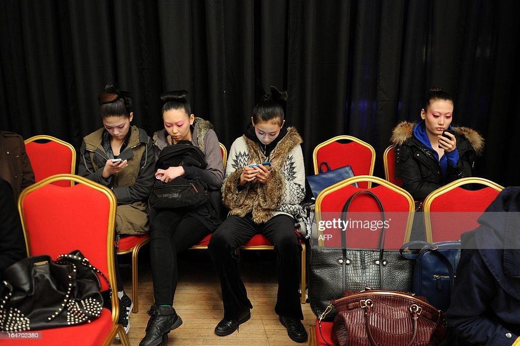 Models look at their cellphones backstage before the Minzu University of China Collection at China Fashion Week in Beijing on March 27, 2013. China Fashion Week runs from March 24 to March 30.