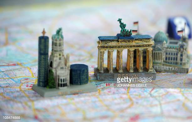 Models of Berlin's landmarks the KaiserWilhelmGedaechtniskirche the Brandenburg Gate and the Reichstag building sitting on a Berlin map and presented...