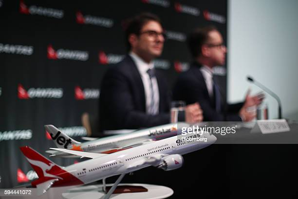 Models of Qantas Airways Ltd and Jetstar Airways Pty aircraft stand on a table as Alan Joyce chief executive officer of Qantas Airways Ltd right...