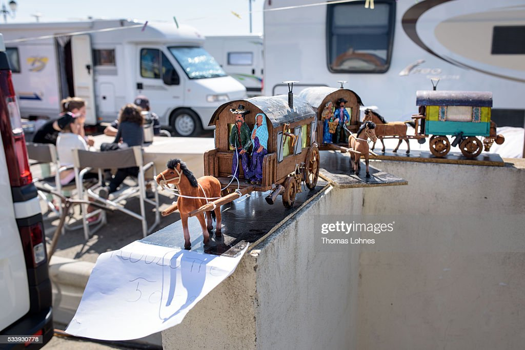 Models of traditional gypsy caravans are for sale stand in front of motorhomes on May 24, 2016 in Staintes Maries de la Mere near Arles, France. Gypsies from all over Europe worship 'Sara the Black', their Saint and patroness, for one week. Sara's statue is situated in the crypt of the church. She wears a multicoloured dress and will carried by the gypsies to the sea at this afternoon.