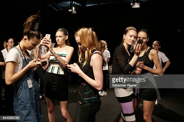 Models on their mobiles are seen backstage ahead of the Irene Luft show during the MercedesBenz Fashion Week Berlin Spring/Summer 2017 at Erika Hess...