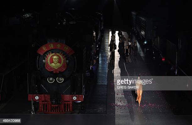 Models parade in creations from the Pierre Cardin spring/summer 2016 collection beside a train bearing an image of late communist leader Mao Zedong...