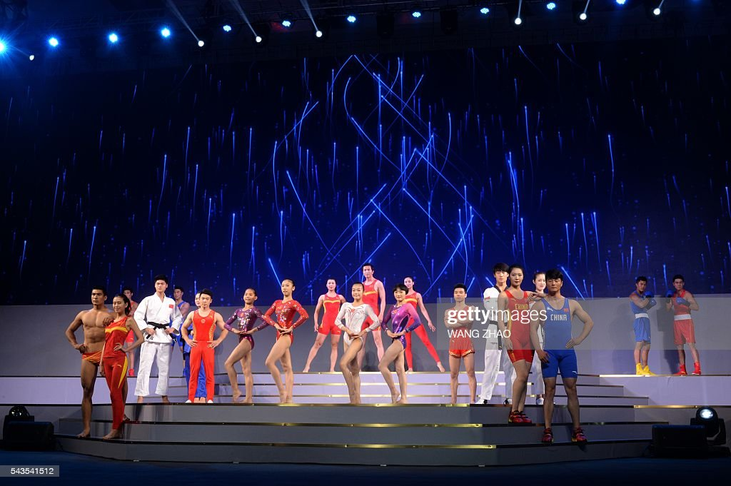 Models parade outfits during a ceremony to unveil the Chinese Olympic team's uniforms for the Rio 2016 Olympic Games, in Beijing on June 29, 2016. The uniforms were unveiled at a ceremony in the Water Cube, the venue for the swimming competition at the 2008 Beijing Olympic Games. / AFP / WANG