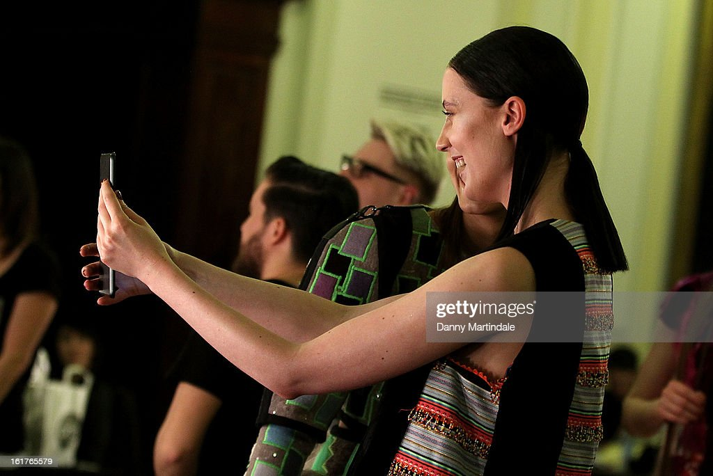 Models play with there iPads backstage at the Nova Chiu show during London Fashion Week Fall/Winter 2013/14 at Freemasons Hall on February 15, 2013 in London, England.