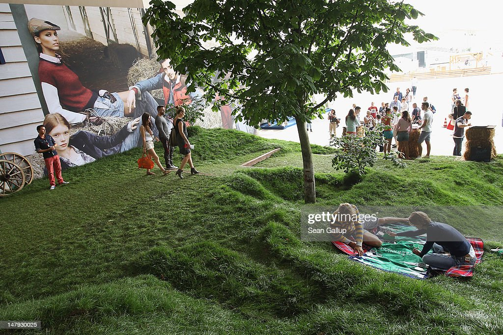 Models playing backgammon recline on real grass as visitors walk past at the Hilfiger Denim stand at the 2012 Bread & Butter fashion trade fair at former Tempelhof Airport on July 6, 2012 in Berlin, Germany. Bread & Butter is the world's largest trade fair for street fashion.