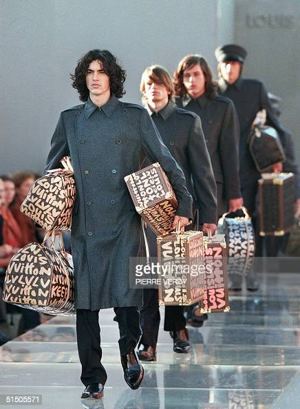 Models playing porter present creations and luggage for Louis Vuitton 11 October 2000 in Paris during the Spring/Summer 2001 readytowear collections