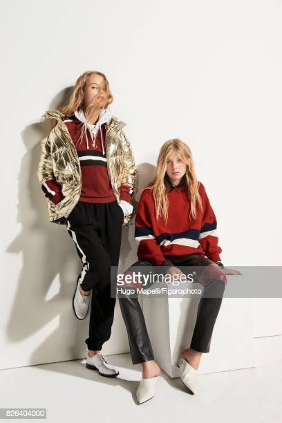 Models pose at a fashion shoot for Madame Figaro on June 30 2017 in Paris France Left Coat sweatshirt parka pants shoes Right Sweater shirt pants...
