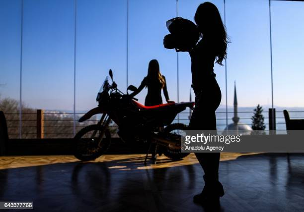 Models pose for a photo near a motorbike and with a motorcycle helmet during an introductory meeting of Motobike exhibition organized by Messe...