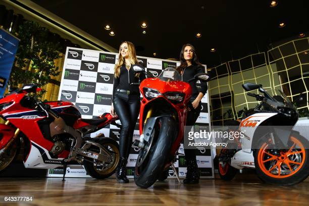 Models pose for a photo near a motorbike during an introductory meeting of Motobike exhibition organized by Messe Frankfurt Istanbul in Istanbul...