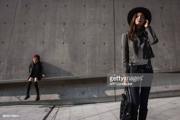 Models pose for photographers during Seoul fashion week at Dongdaemun Design Plaza in Seoul on October 20 2017 For Seoul's flamboyant followers of...