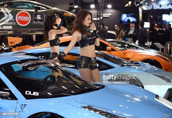 Models pose for photographers next to cars at the 33th Tokyo Auto Salon in Chiba in suburban Tokyo on January 9 2015 About 300000 people will be...