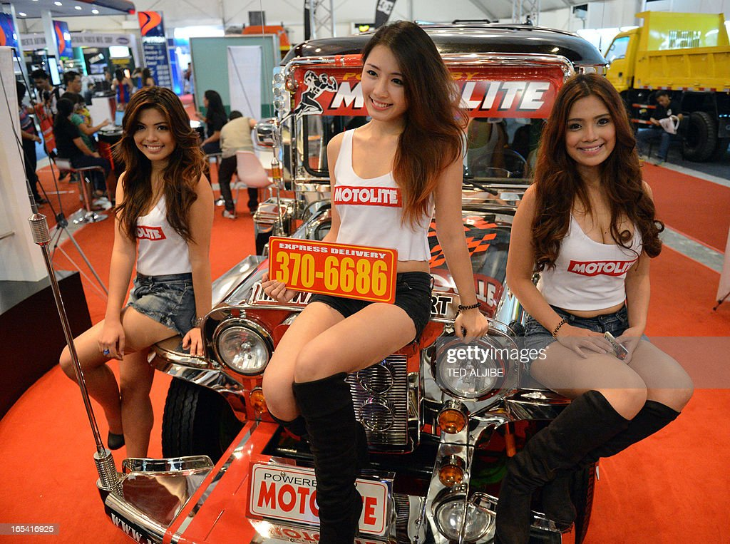 Models pose for photos in front of a passenger jeepney at the auto show in Manila on April 4, 2013. The annual auto show is being held from April 4 to 7 at the world trade center.