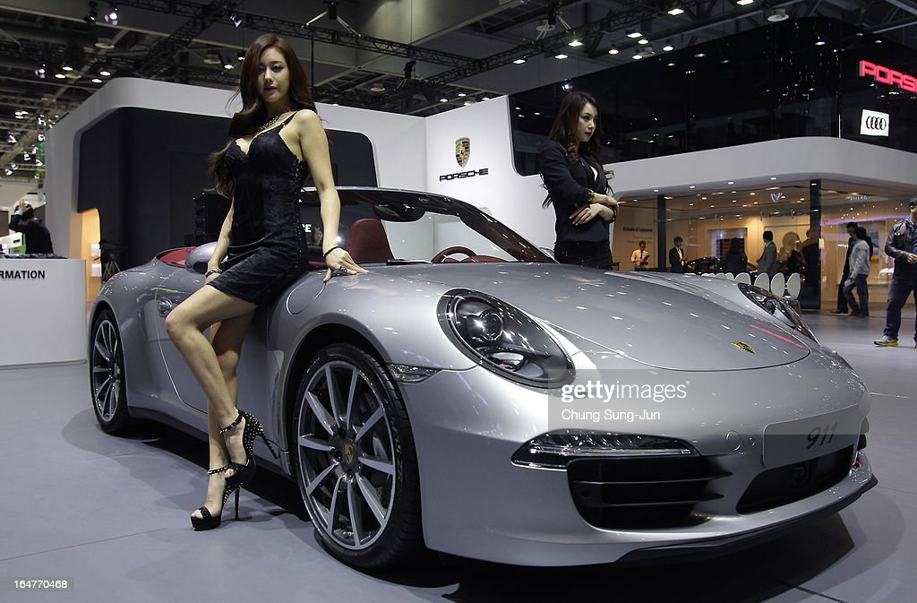 Models pose next to a Porsche 911 at the Seoul Motor Show 2013 on March 28, 2013 in Goyang, South Korea. The Seoul Motor Show 2013 will be held in March 29-April 7, featuring state-of-the-art technologies and concept cars from global automakers. The show is its ninth since the first one was held in 1995. About 384 companies from 14 countries, including auto parts manufacturers and tire makers, will set up booths to showcase trends in their respective industries, and to promote their latest products during the show.