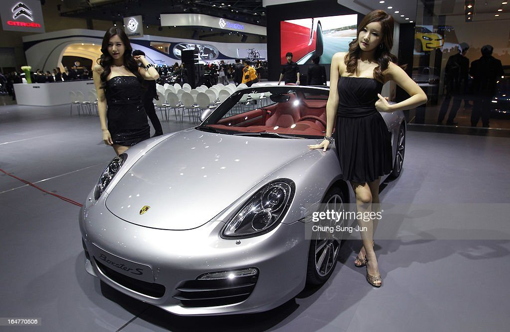 Models pose next to a Porsche Boxster S at the Seoul Motor Show 2013 on March 28, 2013 in Goyang, South Korea. The Seoul Motor Show 2013 will be held in March 29-April 7, featuring state-of-the-art technologies and concept cars from global automakers. The show is its ninth since the first one was held in 1995. About 384 companies from 14 countries, including auto parts manufacturers and tire makers, will set up booths to showcase trends in their respective industries, and to promote their latest products during the show.
