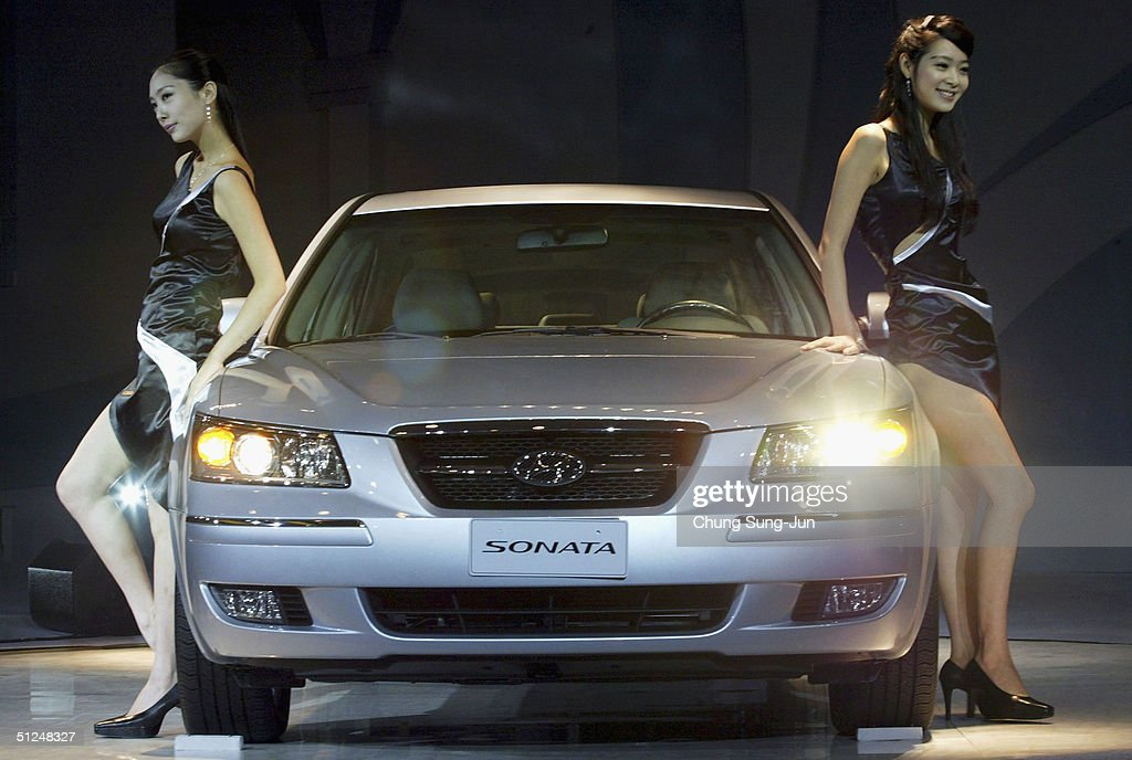 Models pose next to the new midsized sedan 'NF Sonata' unveiled by Hyundai Motor Co on August 31 2004 in Seoul South Korea The new 'NF Sonata' is...
