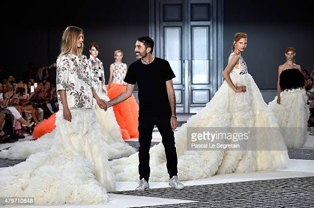 Models pose with designer Giambattista Valli on the runway following the Giambattista Valli show as part of Paris Fashion Week Haute Couture...