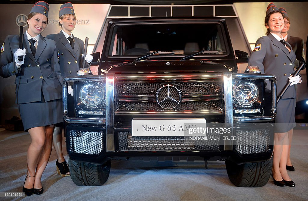 Models pose with the new Mercedes-Benz G63 AMG premium sports utility vehicle (SUV) in Mumbai on February 19, 2013. The G 63 AMG sports a supercharged 5.5-litre V8-engine delivering 400 kw@5500rpm; 760 nm of torque @5000 rpm; 0-100 in 5.4s. AFP PHOTO/Indranil MUKHERJEE