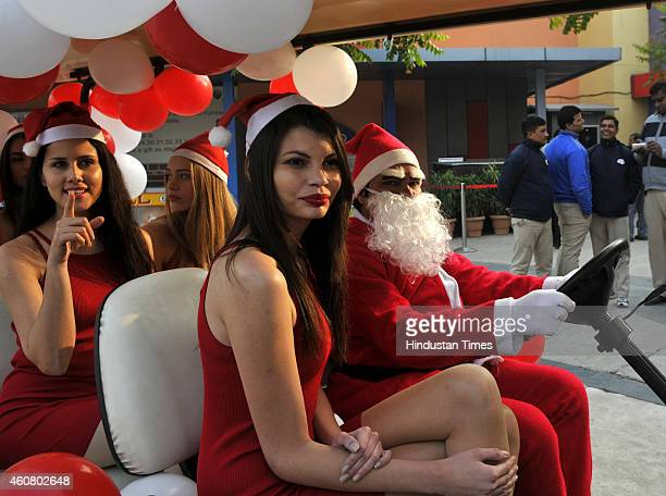 Models posing with a Santa Claus ahead of Christmas at a private mall at sector 38A on December 23 2014 in Noida India