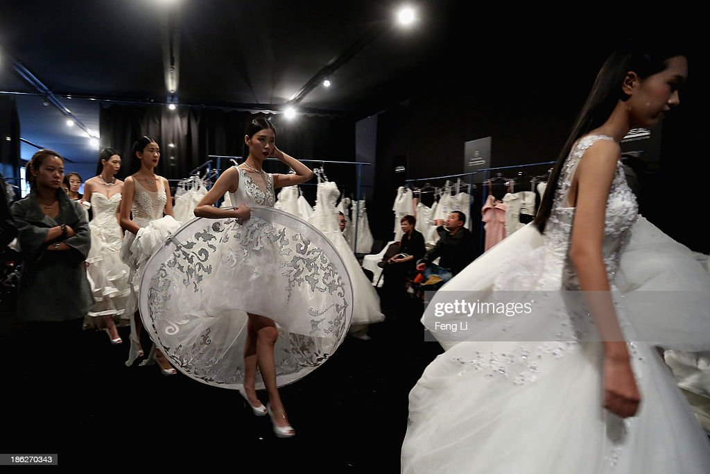 Models prepare backstage ahead of Peng Jing Wedding Dress Collection show during Mercedes-Benz China Fashion Week Spring/Summer 2014 at 751 D-PARK Central Hall on October 27, 2013 in Beijing, China.