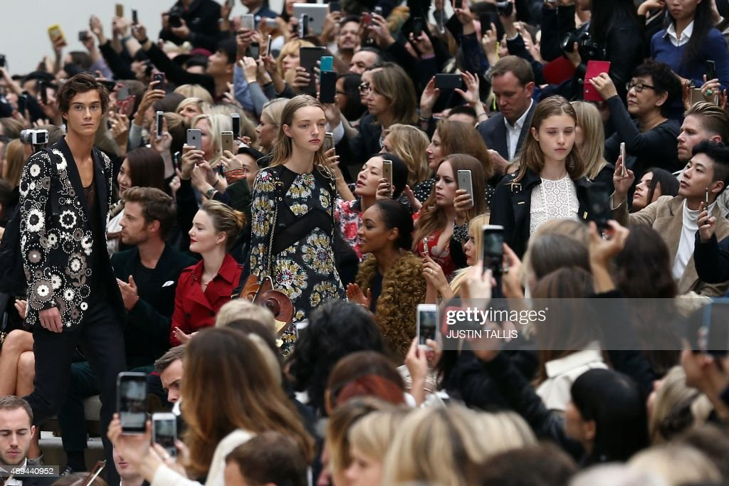 Models present creations as members of the crowd raise their smartphones during the Burberry Prorsum spring / summer 2016 collection show at London...