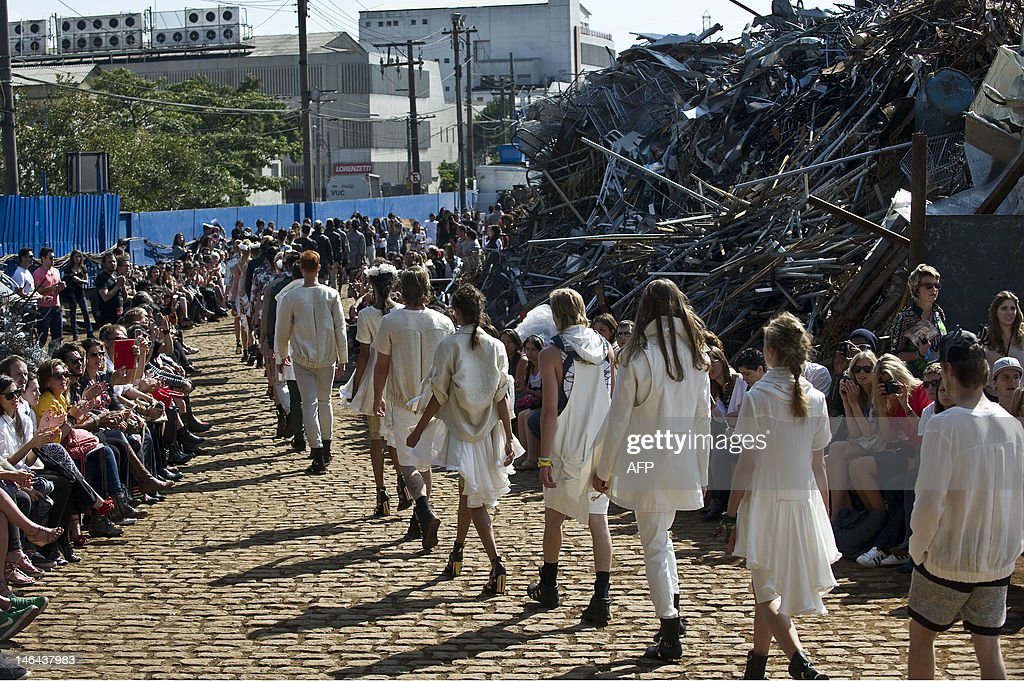 Models present creations by Cavalera 2013 summer collection at a junkyard during the Sao Paulo Fashion Week in Sao Paulo, Brazil, on June 16, 2012. AFP PHOTO / Nelson ALMEIDA