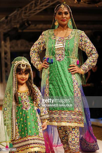 Models present creations by designer Faiza alBalushi during a fashion show organised as part ot the Muscat Festival on February 5 2015 in the Omani...