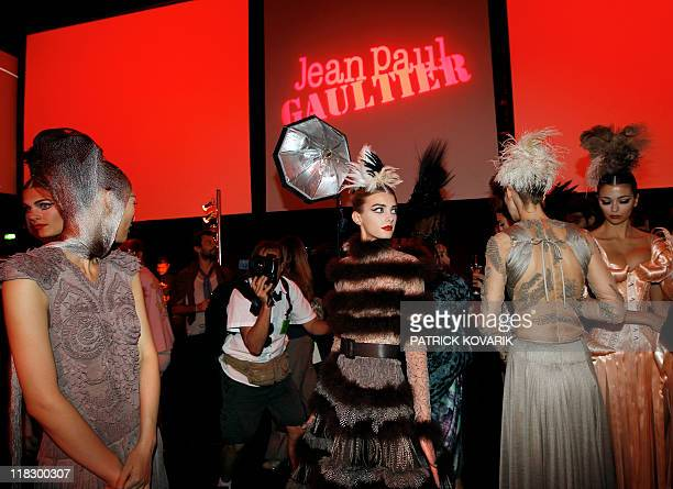 Models present creations by French designer Jean Paul Gaultier as they attend a presentation of Gaultier's new perfume following the Fall/Winter...