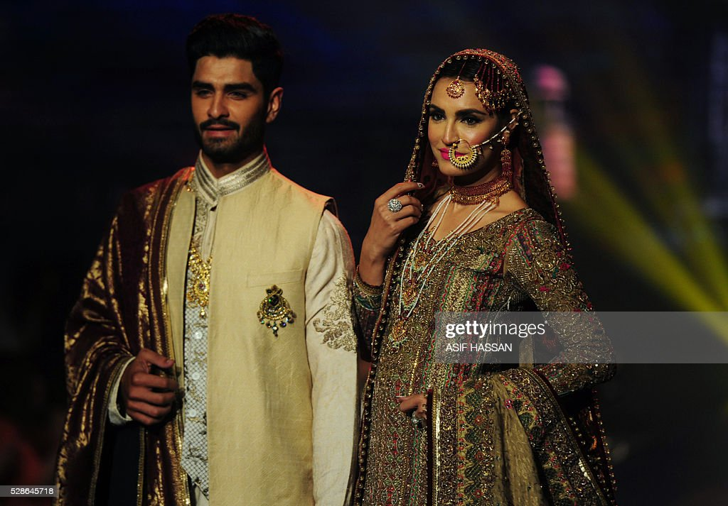 Models present creations by Pakistani designer Fahad Hussayn on the 1st day of Bridal Couture Week-Gold Edition in Karachi on May 6, 2016. / AFP / ASIF